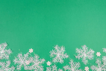 Creative Christmas layout. Snowflakes on green background whit copy space. Border arrangement. Flat lay top view.
