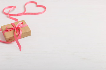 A gift of craft paper and a pink ribbon on a white wooden table. Place for text, copy space, Valentine's day postcard.