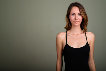 Young beautiful woman wearing sleeveless top against colored bac