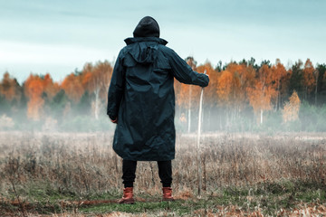 Creative background, Man, man in a black coat in foggy weather, against the background of the forest. The concept of mysticism, autumn, cold, ghost, shepherd.
