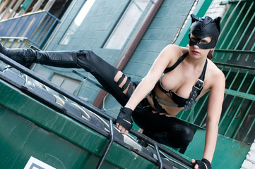 Young woman wearing a leather cat suit and mask