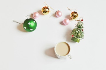 Green, pink, yellow balls, Christmas tree and cup of coffee. Flat lay New Year table. Morning