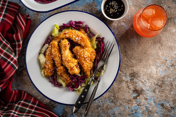 Salad with warm glazing chicken, sprinkled with sesame seeds. Chinese cuisine. Asian culture