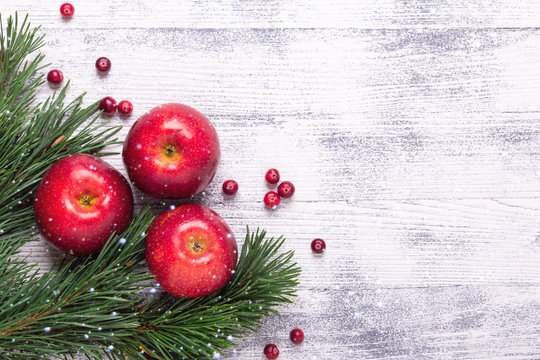 Christmas background with tree branches, red apples and cranberries. Light wooden table. Snowfall drawing effect