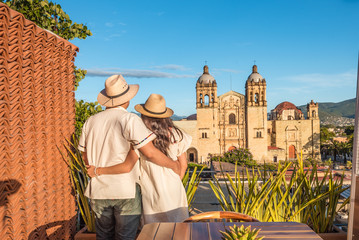 Couple contemplating the Santo Domingo Church during the sunset from a terrace in Oaxaca, Mexico Wall mural