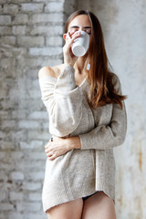 Girl in sweater and long brown hair enjoys drinking tea in a cozy indoor room with her eyes closed