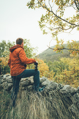 A young man with binoculars in te mountain