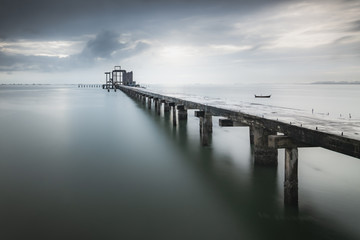 Nature background of a long bridge over an ocean with calm waves and water under blue clouds and sky in the morning