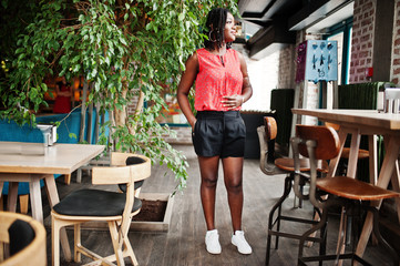 Attractive african american girl posed at cafe against tree.