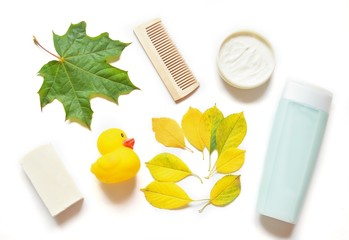 Flat lay shampoo, cream, soap, wooden hair brush and rubber duck