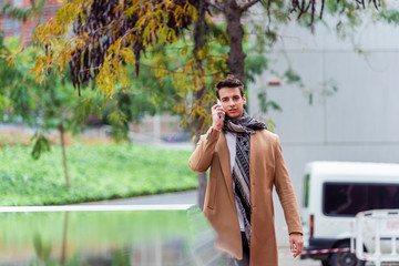 Portrait of stylish handsome young man with coat standing outdoors and leaning on wall using a smartphone