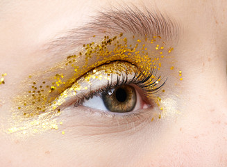 Closeup macro shot of human female eye with yellow smoky eyes beauty makeup.
