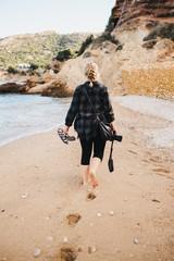 Anonymous woman walking on wet beach