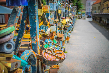 Bright and romantic love locks on the metal fence of the bridge