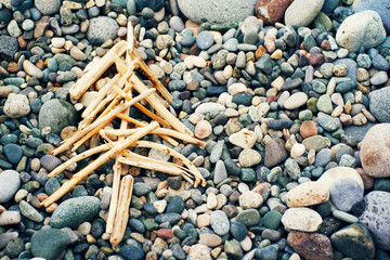 New Year tree from dry sticks on the sea pebble beach. Conceptual image of a New Year tree. Festive cheerful background