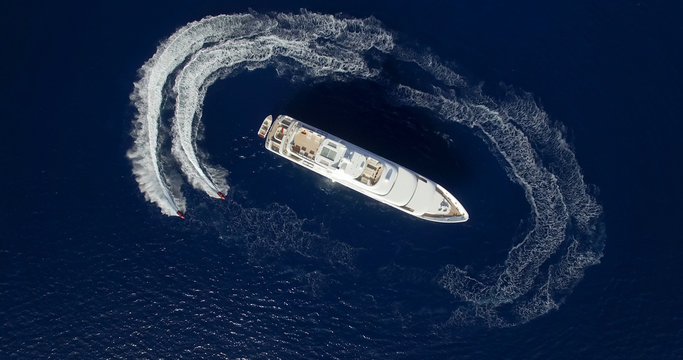 Aerial view of two jet-ski moving around large yacht