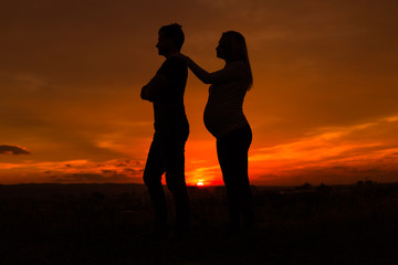 Silhouettes of angry husband and  pregnant wife while they standing outdoor.