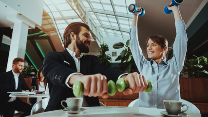 Happy Office Workers Working with Dumbbells