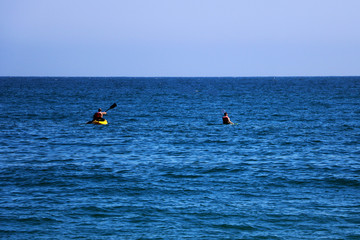 A couple of friends canoeing on a wooden canoe on a sunny day. USA.
