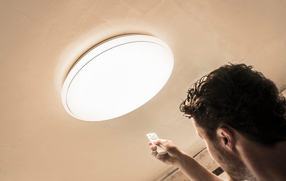 Man using remote control to set the simple big ceiling plafone lamps light intensity, electricity light control concept.