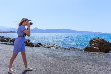 Woman photographer Nature photographer shooting the sea. Travel Concept.