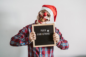 .Young boy dressed as a scary clown in Christmas season. Showing clear hatred for Christmas with a chalkboard that says: