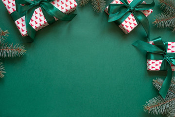 Christmas gift boxes and evegreen branches on green. Invitation. Space for wishes. Top view.