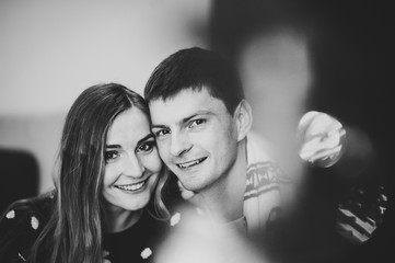 Couple in love next to a Christmas tree. A boy with a girl is celebrating Christmas and enjoys each other on New Year's Eve in a cozy home environment. New Year's love story. Black and white photo.