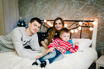 Christmas family! Happy mom, dad and little son in Santa Claus sweaters, lying down. Enjoying love hugs, holidays people. Merry Christmas and Happy New year.