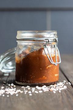 Glass jar of homemade salted caramel sauce with salt over old dark brown wooden background.