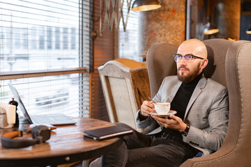 Young man with beard, wearing a suit in the glasses drinking coffee from a Cup. Successful people, businessman in comfortable cafe .
