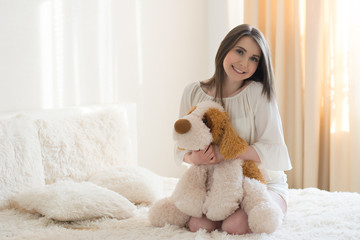 beautiful girl with a plush dog on the bed