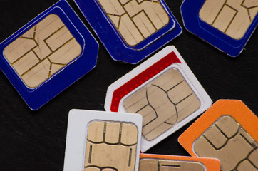 Many cellphone sim cards in different formats for black Background