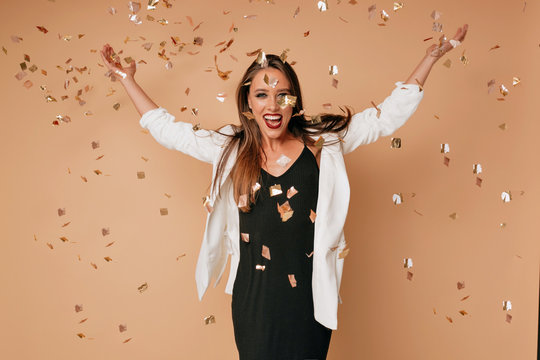 Slim adorable lady with joyful face expression throwing confetti in studio and dancing. Adorable caucasian girl celebrating vacation after party.