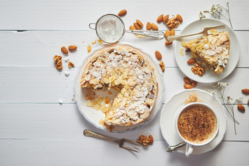 Horizontal shot of a whole round delicious apple cake tart with almond flakes served on wooden...