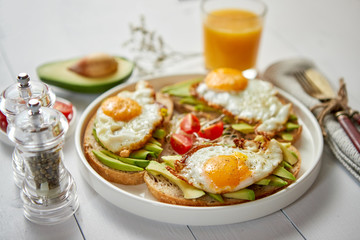 Delicious healthy breakfast with sliced avocado sandwiches with fried egg on top of bread. With orange juice, cherry tomatoes, radish sprouts, salt and peper. Flat lay, top view.