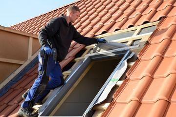 """Dachdecker baut Dachfenster von """"Velux"""" auf dem Bau in rote Dachziegel Dächer ein"""