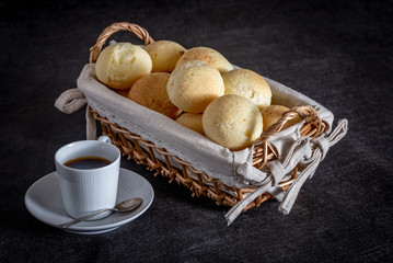 Brazilian homemade cheese bread, AKA 'pao de queijo' in a rustic basket and a cup of coffee