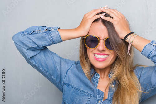 a0a1d60ac56 Young adult woman over grunge grey wall wearing retro sunglasses suffering  from headache desperate and stressed because pain and migraine. Hands on  head.