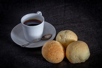 Brazilian homemade cheese bread, AKA 'pao de queijo' in a rustic background and a cup od coffee