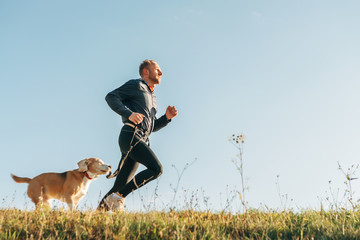 Sport activity with pet. Canicross exercises. Man runs with his beagle dog
