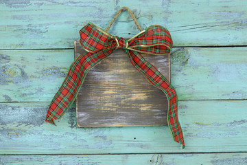 Blank wood sign with red and green plaid Christmas bow hanging on antique rustic teal blue wooden door; holiday background with painted copy space
