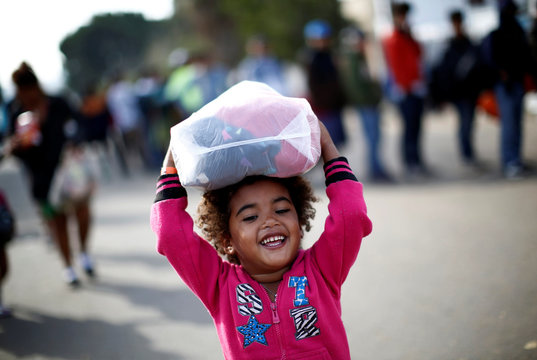A migrant girl from Honduras, part of a caravan of thousands traveling from Central America en route to the United States, smiles as she carries donated clothes which she and her family received outside a shelter in Tijuana