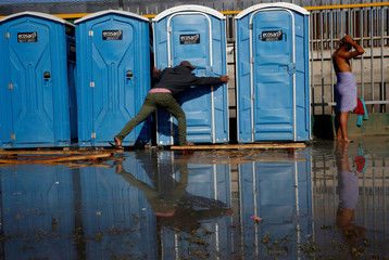 A migrant, part of a caravan of thousands traveling from Central America en route to the United States, tries to reach a restroom as he avoids to wet in dirty water at a shelter in Tijuana