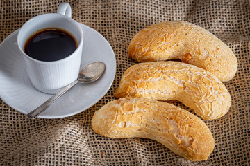 Brazilian homemade cheese bread, AKA 'chipa' isolated a rustic background and a cup of coffee.