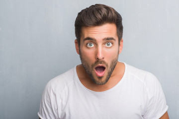 Handsome young man over grey grunge wall scared in shock with a surprise face, afraid and excited with fear expression