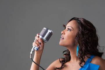 Young African-American woman in a blue dress singing into old microphone