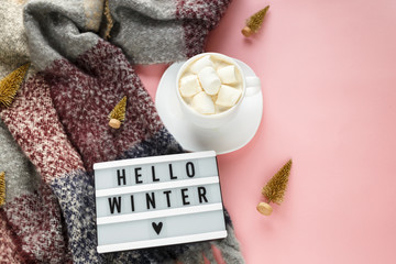 Warm, cozy winter clothing, scarf, lightbox and cup of coffee with white marshmallow as frame on pastel  pink background. Christmas concept flat lay. hello winter title