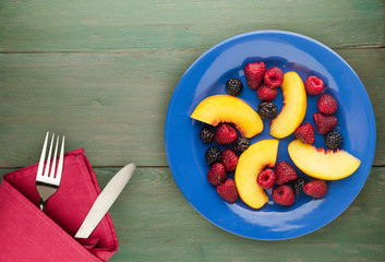 dietary, healthy food. blackberry, raspberry, nectarine on a plate on a plate. Vegetarian food on a wooden background