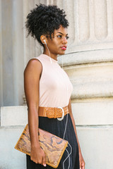 Young black woman with afro hairstyle, wearing sleeveless light color top, belt, carrying small leather briefcase, standing by column outside office building, listening music with earphones, thinking